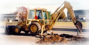 A yellow excavator digging a hole